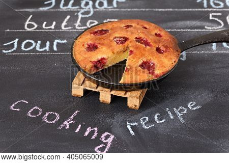 Sour Cherry Cake In A Pan On A Wooden Trivet. Ingredients Written In Chalk On The Background.