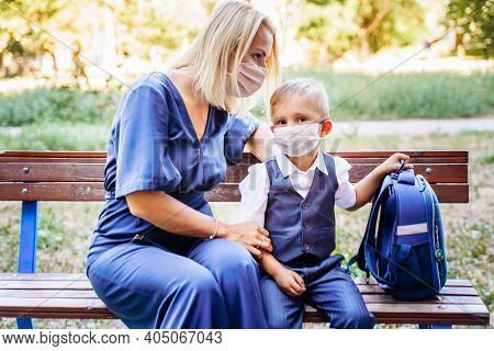 Mom And Her Son, A Schoolboy, Are Sitting On A Bench In The Yard. They Put On Medical Masks To Prote