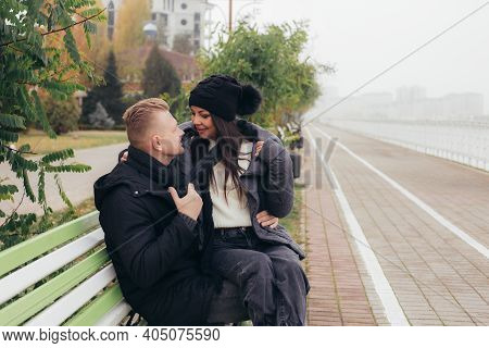 A Young Couple In Love Sits On A Bench On The Embankment, Smiling And Looking Into Each Others Eyes