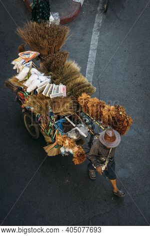 Top View Of Street Vendor Pulling A Cart With Brooms Dusters And Other Cleaning Supplies Selling The