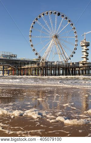 Ferris Wheel On De Pier In The Hague With Blue Sky And Calm Water At The Beach Of Scheveningen, Neth