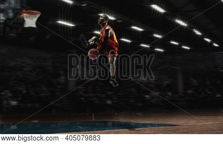In High Flight. African-american Young Basketball Player In Action And Motion In Flashlights Over Da