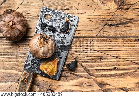 Fermented Bulbs And Cloves Of Black Garlic. Wooden Background. Top View. Copy Space