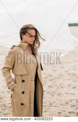 Fashion Portrait. Female Tenderness. Autumn Melancholy. Pensive Woman In Beige Trench Coat With Flyi