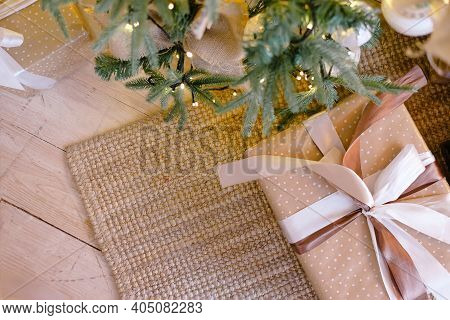 Beige Square Boxes With Gifts Decorated With Ribbons Stand Under A Christmas Tree Decorated With Gol