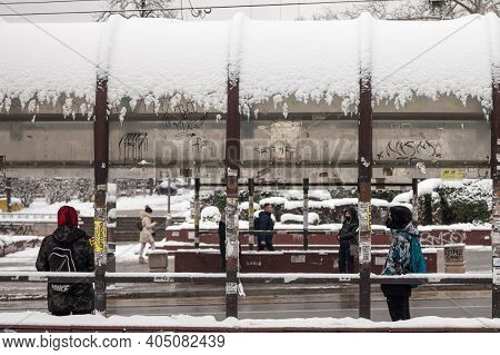 Belgrade, Serbia - January 17, 2020: Youngsters Waiting Their Bus At A Stop In Belgrade During A Sno