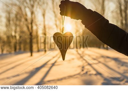 Womans Silhouette Hand Holding A Wooden Heart On Winter Snowy Forest Evening Blurred Background. Lov