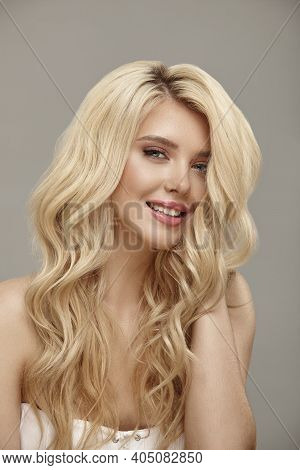 Vertical Shot Of Pretty Smiling Woman Portrait With Curly Blonde Hair And Clean Skin, Studio Beauty