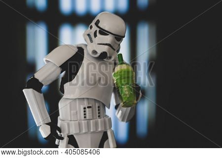 JAN 25 2021: Star Wars Imperial Stormtrooper looks down straw of a Starbucks Frappuccino - humor - Hasbro action figure