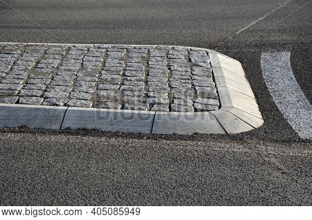 Roundabout Of Paving Of Gray Granite Cubes In A Rolled Sill Closer To The Center. Beveled Concrete C