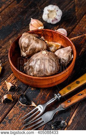 Bulbs And Cloves Of Fermented Black Garlic In A Plate. Dark Wooden Background. Top View