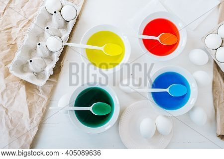 Flat Lay Preparing For Easter, Dyeing Eggs With Liquid Food Coloring. Different Colors In Different