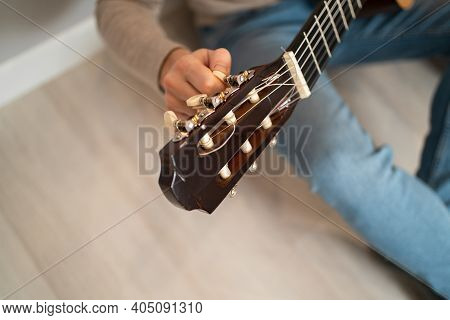The Guy Is Tuning The Guitar. Close-up Of A Guitar Fretboard. Man Twists The Tuning Pegs At The Guit