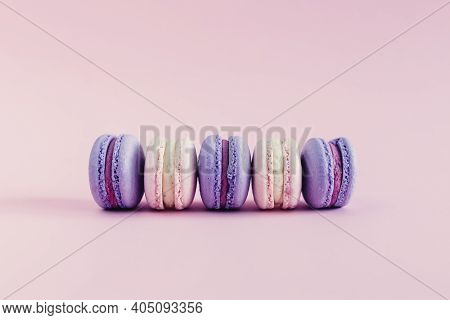 Tasty French Macarons On A Pink Pastel Background. Pink And Violet Macarons.