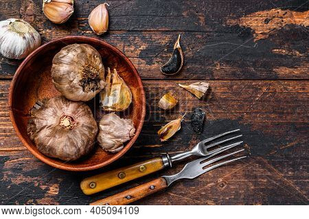 Bulbs And Cloves Of Fermented Black Garlic In A Plate. Dark Wooden Background. Top View. Copy Space