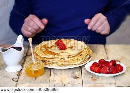 A Plate With Pancakes, Strawberries, Honey And Jam On A Wooden Table. Pancake Week. The Man At The T