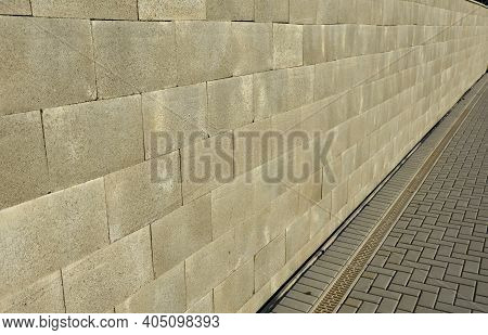 Concrete Wall Made Of Smooth Blocks. High Dividing Noise Wall Of The Yard. Under The Wall Is A Longi