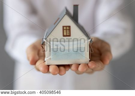 House With Medical Mask In Children`s Hands. Coronavirus Covid-19 Pandemic. Stay Home Concept