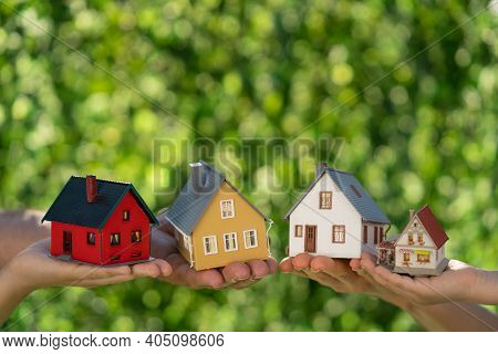 Family Holding Eco Houses In Hands Against Spring Green Background. Real Estate And Earth Day Holida