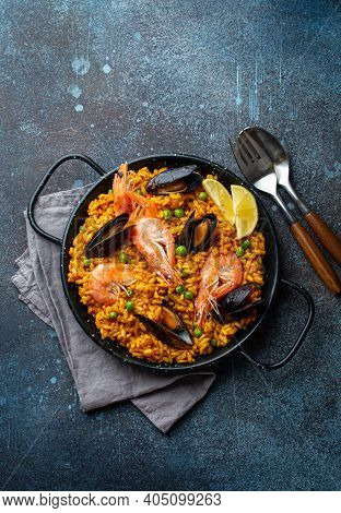 Classic Dish Of Spain, Seafood Paella In Traditional Pan On Rustic Blue Concrete Background Top View