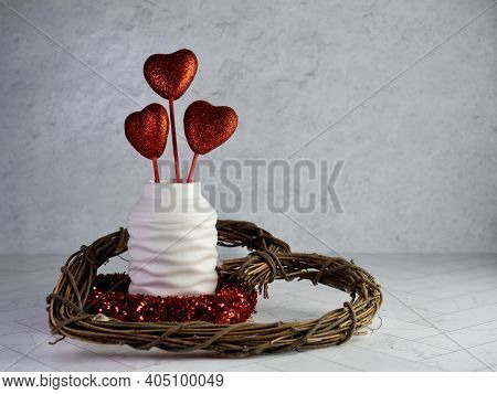 Valentine's Day Decor, A Wooden Heart Wreath, Red Glittery Heart Wreath And A White Vase Filled With