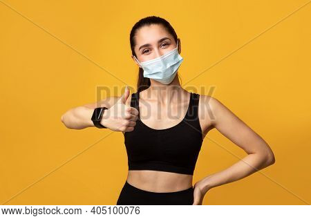 New Rules. Portrait Of Athletic Woman Wearing Disposable Protective Face Mask While Exercising In A