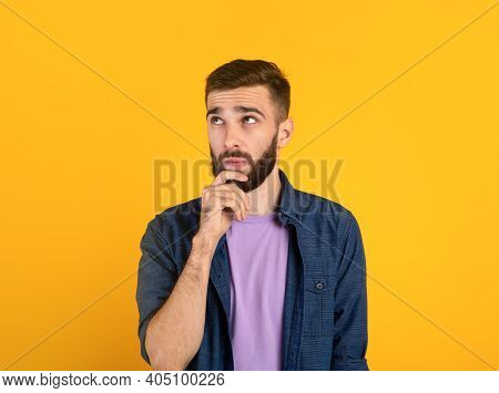 Portrait Of Pensive Young Bearded Man Touching His Chin, Deep In Thought Over Orange Studio Backgrou