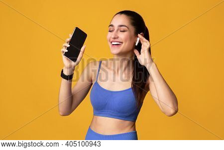 Enjoying Favorite Playlist During Workout. Happy Young Woman Wearing And Touching Wireless Earbuds,