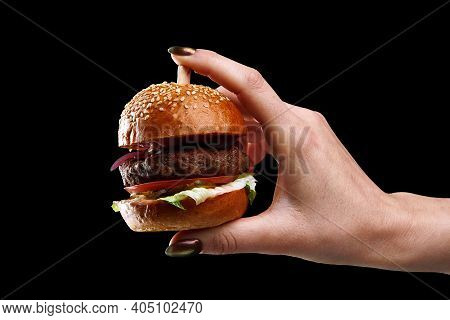 Female Hand Holding Mini Burger As A Christmas Tree Toy On Black Background