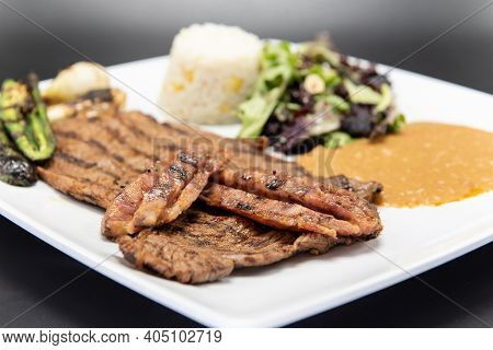 Grilled Carne Asada Steak Topped With Chorizo Served On A Plate With Rice And Beans.