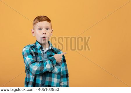 Amazed Red-haired School Boy In Plaid Shirt Aiming At Copy Space Over Yellow Studio Background. Shoc