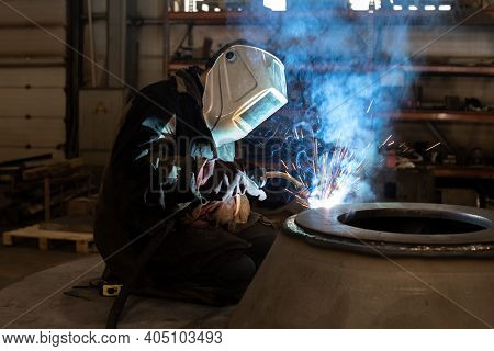 A Welder In A Protective Mask Welds Parts, Welding Sparks And Smoke In The Production Area. Welder A
