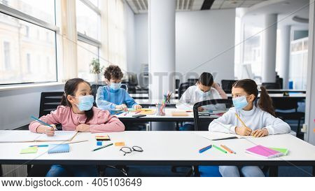 Multicultural Schoolchildren Wearing Disposable Medical Masks Sitting At Table In Classroom, Keeping