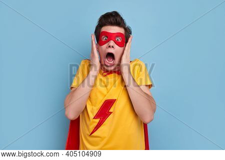 Thrilled Young Man In Superhero Costume And Mask Looking At Camera With Mouth Opened And Expressing