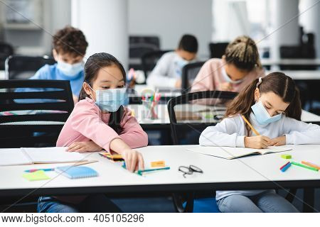 Education During Pandemic. Diverse Girls Sitting At Table In Classroom At School Or Kindergarten, We