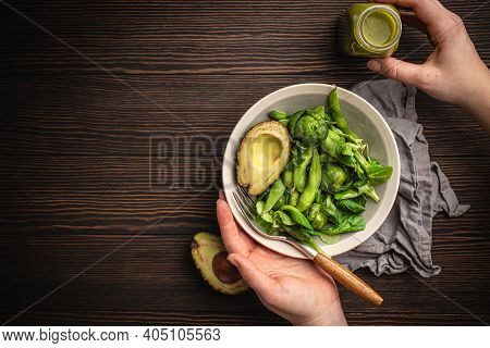 Bowl Of Healthy Salad In Female Hands From Above And Green Detox Smoothie In A Bottle On Wooden Back