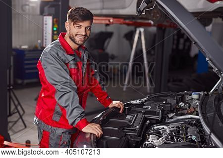 Happy Young Man In Mechanic Uniform Smiling And Looking At Camera While Standing Near Vehicle With O