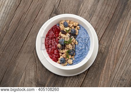 Breakfast Smoothie Bowl With Granola On Wooden Background