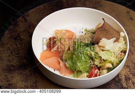 Caesar Salad With Salmon Fish On White Bowl