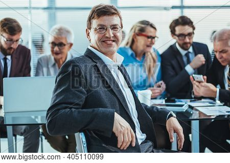 Confident Business Man Sitting In Front Of An Office Desk