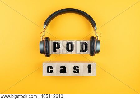 Word Podcast On Wooden Blocks And Headphones On Orange Background, Podcasting Concept
