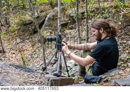 Portrait Of A Young Man Setting Up His Professional Photo Equipment, Dslr Camera And Tripod, In A Cl