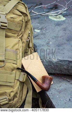 Close Up Advertising Style Shot Of A Green Army Tactical Backpack, A Wooden Vintage Pipe And A Noteb