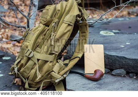Close Up Advertising Style Shot Of A Green Army Tactical Backpack, A Paper Notebook And A Vintage Pi