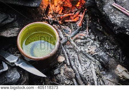 Close Up Shot From Above Of A Small Green China Tea Cup With Water In It And A Camping Knife At The