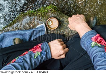 Very Close Up From Above Of A Girl Sitting Cross Legged On A Rock On The Shore Of A River, A Small T