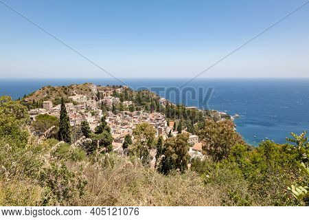 The Hilltop Town Of Taormina, Idyllicaly Perched On A Rocky Cliff High Above The Sea, Sicily, Italy