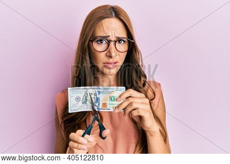Young brunette woman cutting dollars with scissors for currency devaluation clueless and confused expression. doubt concept.