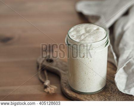 Wheat Sourdough Starter. Glass Jar With Sourdough Starter On Wooden Cutting Board Over Wooden Tablet