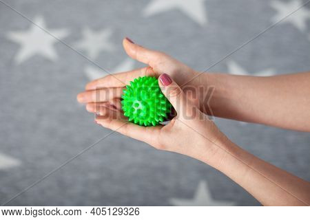 Close-up Two Female Palms Hold A Green Spiked Massage Ball Against A Gray Carpet With White Stars